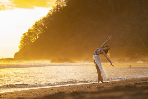 Teenage girl practicing gymnastic at seafront by sunset, Jaco Beach, Costa Rica - AMUF00016