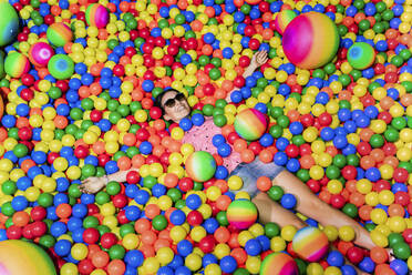 Portrait of happy woman lying among many colourful balls - GEMF03471