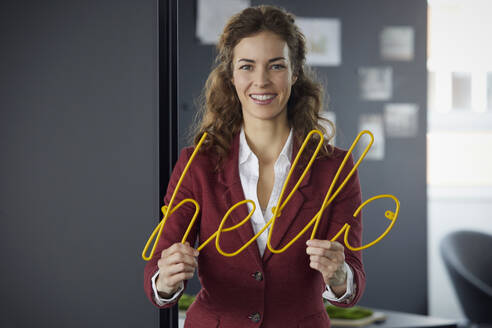 Portait of smiling businesswoman holding 'hello' neon sign in office - RBF07074