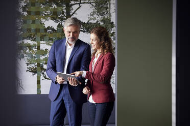 Businessman and businesswoman working together on tablet in office - RBF07098