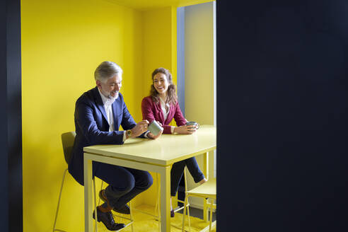 Businessman and businesswoman having a coffee break in office cubicle - RBF07101