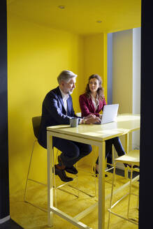 Businessman and businesswoman working together on laptop in office cubicle - RBF07104