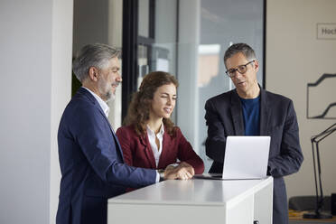 Two businessmen and businesswoman working together on laptop in office - RBF07110