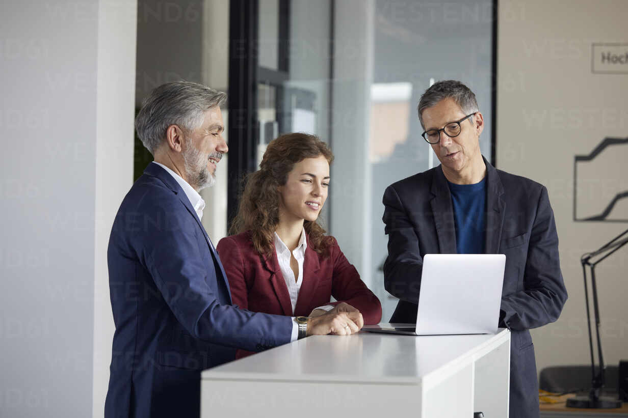 Two businessmen and businesswoman working together on laptop in office - RBF07110 - Rainer Berg/Westend61