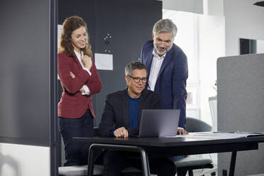 Two businessmen and businesswoman working together on a project in office - RBF07119