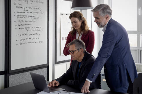 Two businessmen and businesswoman working together on a project in office - RBF07128
