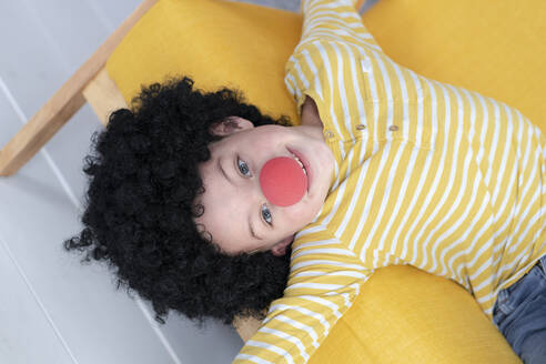 Boy with red clown nose and black hair on yellow couch - HMEF00787