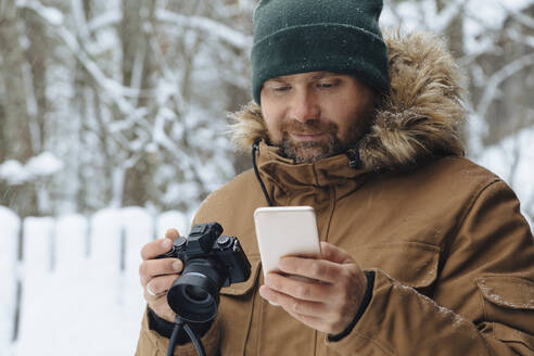 Portrait of bearded man looking with digital camera looking at cell phone in winter - KNTF04482