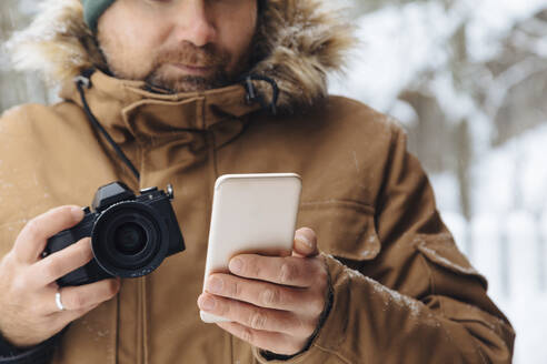Crop view of man with digital camera looking at cell phone in winter - KNTF04485