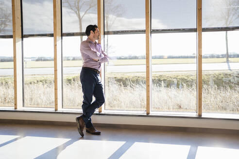 Businessman looking out of window in open-plan office - DIGF09400