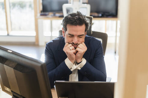Frustrated businessman sitting at desk in office - DIGF09472