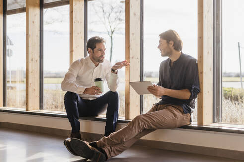 Two businessmen with tablet talking at the window in open-plan office - DIGF09484