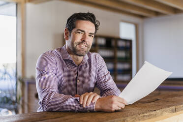 Portrait of smiling businessman with document in wooden open-plan office - DIGF09493