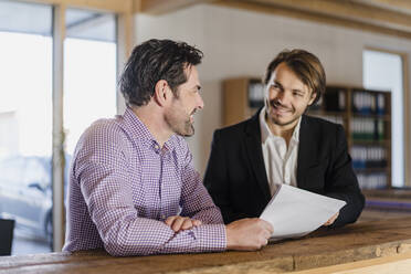 Two smiling businessmen with documents talking in wooden open-plan office - DIGF09496