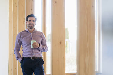 Portrait of smiling businessman holding cup in wooden open-plan office - DIGF09511