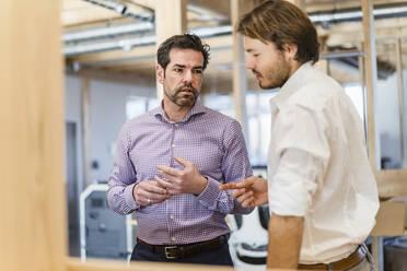 Two businessmen talking in wooden open-plan office - DIGF09520