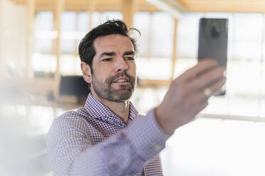 Businessman taking a selfie in wooden open-plan office - DIGF09523