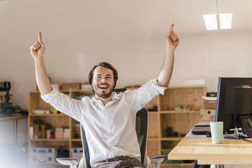 Businessman cheering at desk in office - DIGF09532