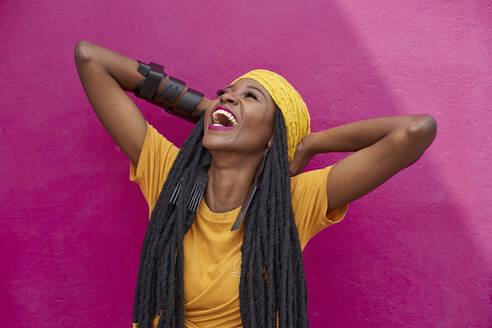 Portrait of woman with long dreadlocks laughing in front of a pink wall - VEGF01679