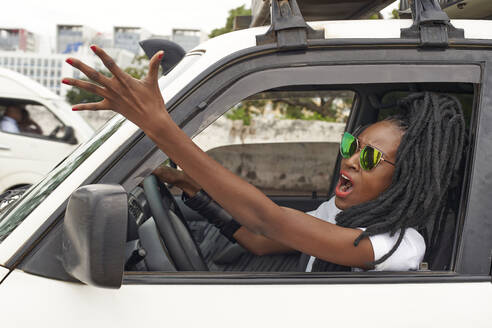 Portrait of angry woman with dreadlocks driving car - VEGF01694