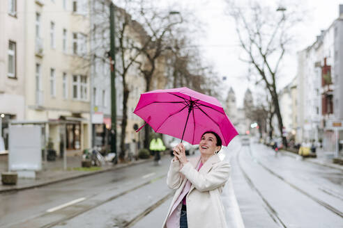 Smiling woman with pink umbrella walking on street - VYF00048