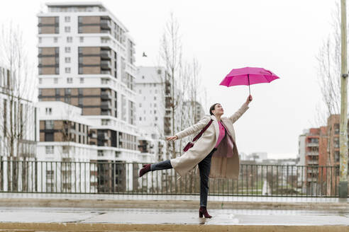 Smiling woman with pink umbrella walking in the city - VYF00051
