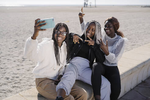 Portrait of happy teenage girlfriends taking a selfie at the beach - MPPF00586