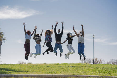 Portrait of happy teenage girlfriends and young man jumping on a meadow - MPPF00634