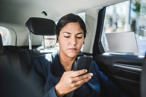 Businesswoman using smart phone while traveling in car - MASF16949