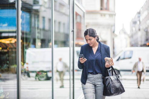 Businesswoman using phone while walking by building - MASF16952