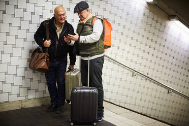 Senior gay couple with luggage using mobile phone while standing in subway - MASF17105