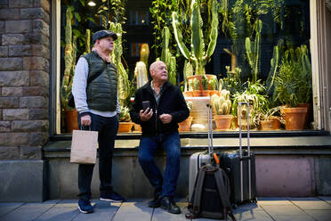 Full length of senior gay couple with luggage waiting outside plant store at night - MASF17120