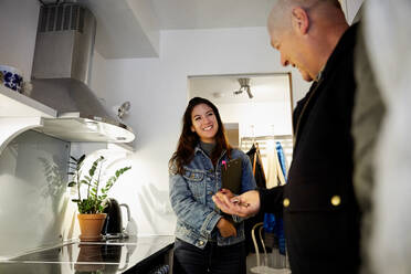 Smiling senior man holding keys while standing with female owner in kitchen - MASF17129