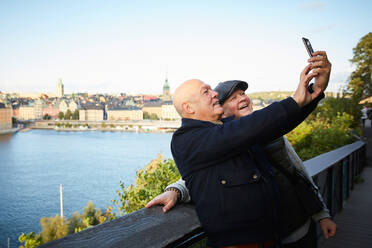 Smiling friends taking selfie with mobile phone against river in city - MASF17144