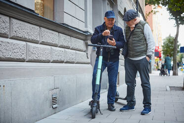 Full length of gay couple using mobile phone while standing with push scooters on sidewalk in city - MASF17162