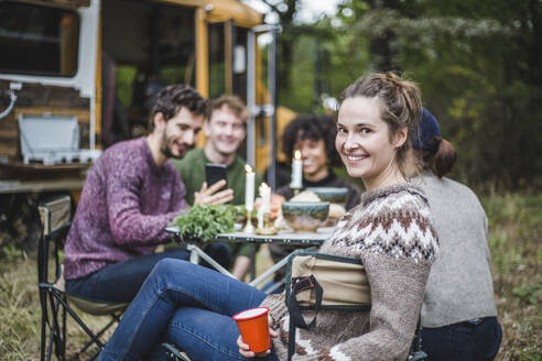 Portrait of smiling blond woman sitting friends at table by caravan in forest during camping - MASF17285