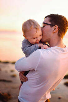 A young father kissing his baby boy. - CAVF76991