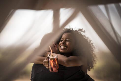 Happy woman holding fresh ice tea drink hugging man - MJRF00251