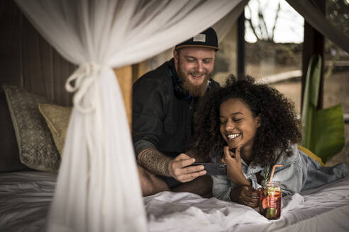 Happy couple on bed in a lodge with smartphone and fresh ice tea - MJRF00263