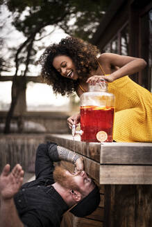Happy woman pouring ice tea into boyfriend's mouth - MJRF00266