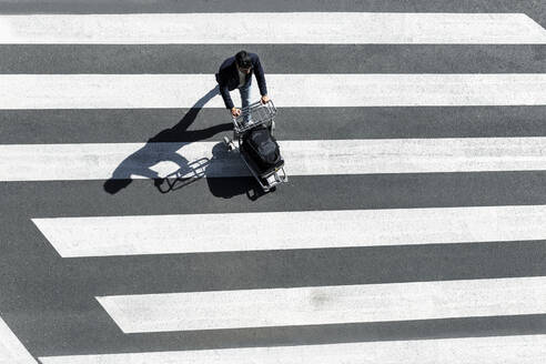 Man on zebra crossing pushing baggage cart, top view - JPTF00478