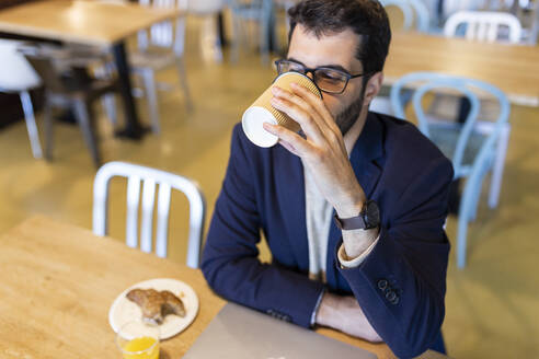 Man drinking coffee in a coffee shop - JPTF00484