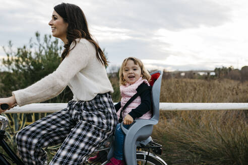Woman riding bicycle in the countryside with happy daughter in child's seat - JRFF04134