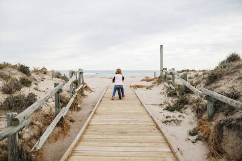 Rear view of toddler girl with balance bicycle on a boardwalk in the dunes - JRFF04146