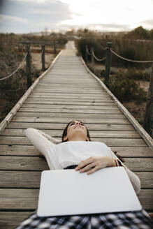 Woman lying on a boardwalk in the countryside with laptop - JRFF04155