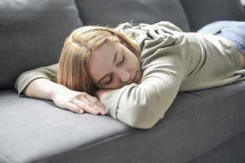 Portrait of blond young woman napping on the couch - BFRF02198