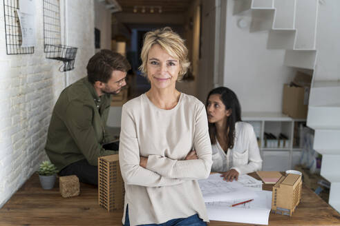 Portrait of confident mature woman in architectural office with colleagues in background - AFVF05653
