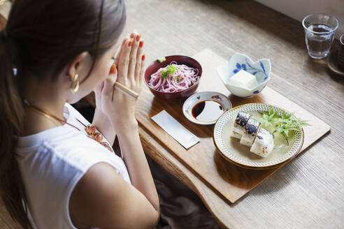 High angle view of Japanese woman sitting at a table in a Japanese restaurant, eating. - MINF14144