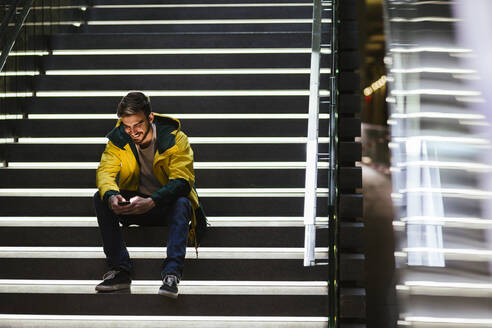 Smiling man sitting on stairs in subway station using cell phone - LJF01407