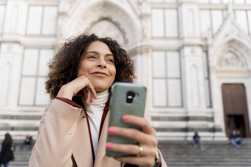 Woman with smartphone at Santa Croce church, Florence, Italy - FMOF00907
